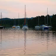 Sunset over sailboats at rest at the northern end of Lake Windermere.