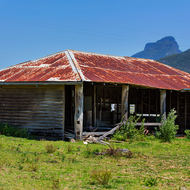 Old rusting farm shed with Mount Barney behind.