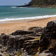 Surfers out a Dolphin Point and the beach of Tea Tree Bay.