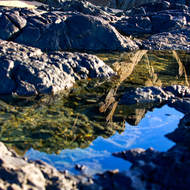 Reflections of the rocky crag of the Hells Gates point in a tide pool.