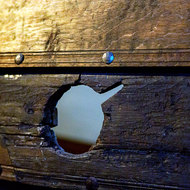 Detail of the riveted planking and oar hole of an exhumed Viking boat.