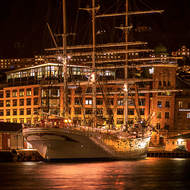 Statsraad Lehmkuhl sailing ship across Vagen harbor at night.