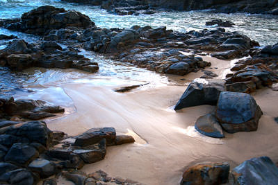 Thumbnail image of Sunlight reflected off sand and sea amongst rocks.