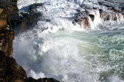 Thumbnail image ofWaves pounding against the rocky shore.
