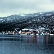 The small town of Finnsnes at the foot of misty, snowy mountains.