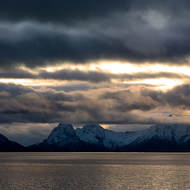 Dark clouds, mountains and sun reflected on the sea.