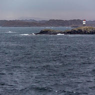 Lighthouses and navigation aids line the navigation channel between outcrops.