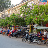 Cambodian tuk tuks, motorcycles and even a car under a cacophony of cables.