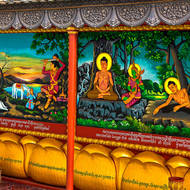 Wall of images telling the Ramayana story in Wat Prom Rath, the young Buddha cutting off his hair.