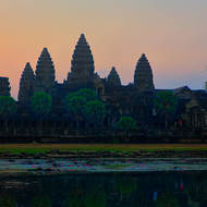 With sunrise close the details of the west side of Angkor Wat and the pond are lightening.