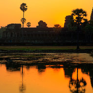 Sun rising behind the chedis of Angkor Wat and reflected in the pond.