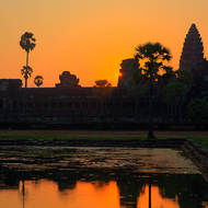 Sun peeps past a chedi of Angkor Wat.