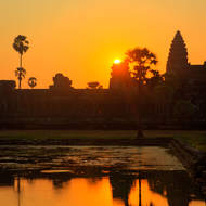 Ball of sun appears over a chedi of Angkor Wat.