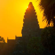 Rising sun creeps up and peeps past a chedi of Angkor Wat.