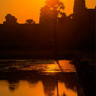 The rising sun tops Angkor Wat and reflects in the pond on the western side.