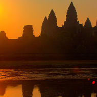 The sun rises over Angkor Wat and the pond on the western side.