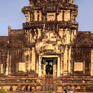 A Buddha image stands inside an entrance tower on the western side of Angkor Wat.
