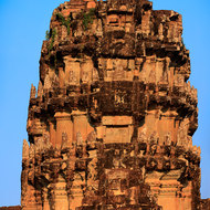 Detail of the main tower on the western entrance to Angkor Wat, showing weathered stone carvings and bas reliefs.