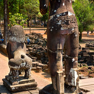 Standing Buddha image (head looted) and lion in the grounds around Bayon in the Angkor Thom complex.