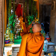 A monk photographs a standing Buddha image in the Gallery of 1000 Images of Lord Buddha in Angkor Wat.