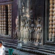Bas relief of Apsara dancers on the inner wall of enclosure II of Angkor Wat above modern traditional dancers waiting to perform.