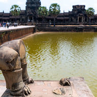 Lion hindquarters, front looted, on the bridge over the western moat of Angkor Wat.