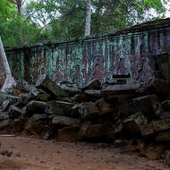 Collapsed columns from an outer building in front of a bas relief on a gallery wall of Ta Prohm.
