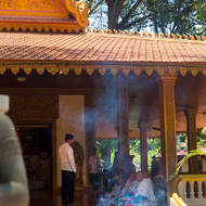 Monks receiving alms behind a screen of incense smoke at Preah Angchek temple in Siem Reap.