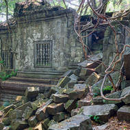 Fallen masonry, trees and roots by the south entrance through the outer enclosure of Beng Mealea temple.