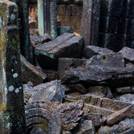 Collapsed masonry and stone carvings in the inner sanctuary of the Prasat Thom temple.