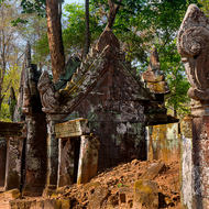 Entrance portico and tower of collapsed Prasat Kra Chap temple in the jungle.