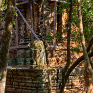 Elephant statue on the lower pedestal at Prasat Damrei temple in front of the central tower propped up and supported from further collapse.