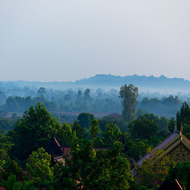 Morning mist hangs over the trees and houses in Siem Reap.