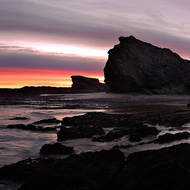 Sunrise is imminent behind the rocks at the mouth of Currumbin Creek.