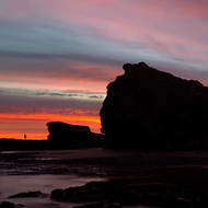 A lone angler silhouetted by sunrise on the rocks at the mouth of Currumbin Creek.