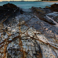 Morning sun reflects off wet rocks highlighting patterns, Currumbin beach as backdrop.