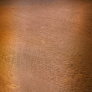 Patterns in the sand in the low, morning light.