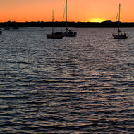 Last light of sunset silhouettes the yachts on the Clarence River.
