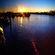The sun is low, close to setting, over the small boat harbor at Yamba.