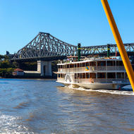 Kookaburra Queen paddle steamer running down river under the Story Bridge.