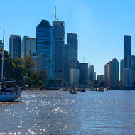 Yachts at rest on the Brisbane River with downtown Brisbane as backdrop.