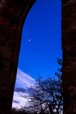 Thumbnail image ofThe moon through a window opening in the church.
