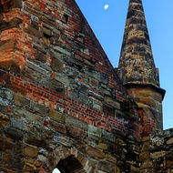The moon nestles beside a corner spire of the Port Arthur church.