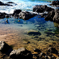 Calm rock pool with sand ripples at Mayfield Beach.