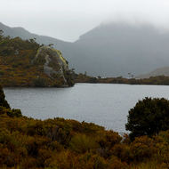 Glacier Rock protrudes into Dove Lake, behind Cradle Mountain is shrouded by cloud.