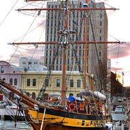Sailing boat in Constitution Dock as the sun sets behind Hobart town.