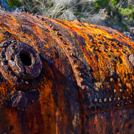 Riveted shell of an old boiler, rusting away on the beach.