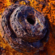 Rust textures of a pipe connection in the shell of an old boiler.