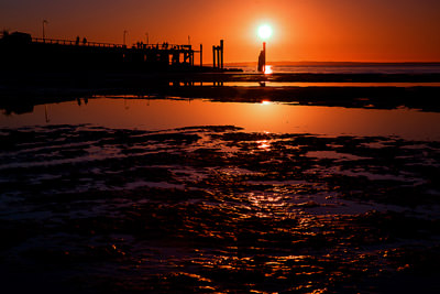 Thumbnail image ofJetty reflected in a tidal pool at sunset.