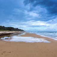 Swimming at Nambucca beach under a dark and stormy sky.